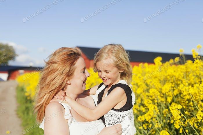 Glückliche Frau trägt Tochter auf Raps Feld
