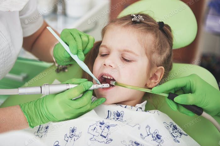 pediatric dentist and assistant making examination procedure for smiling cute little girl