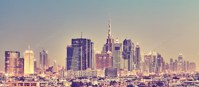 Color toned panoramic picture of Dubai skyline at sunset.