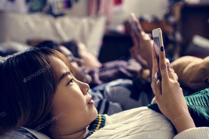 Teenage girls using smartphones on a bed internet in slumber party