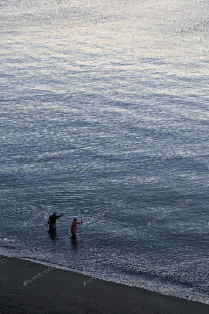 A view from above of a guide and a fly fisherman at the water's edge fishing for salmon and sea run