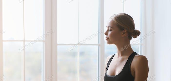 Porträt des harmonischen jungen Mädchens mit geschlossenen Augen gegen Fenster