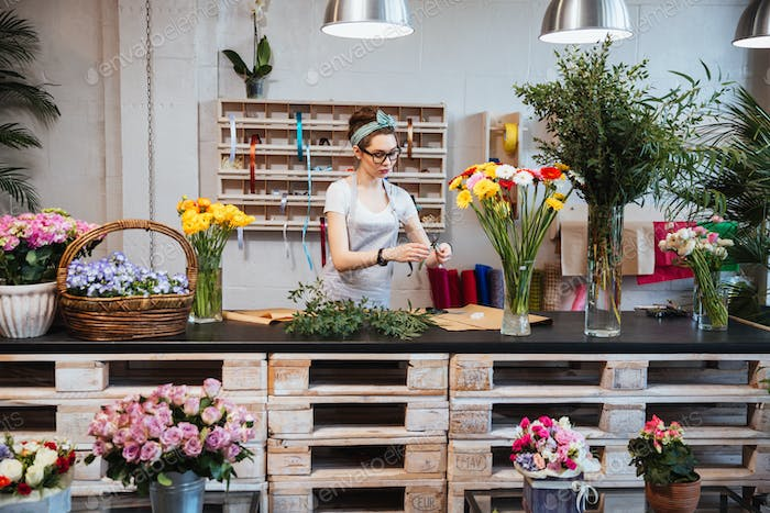 Cute concentrated female florist working in flower shop