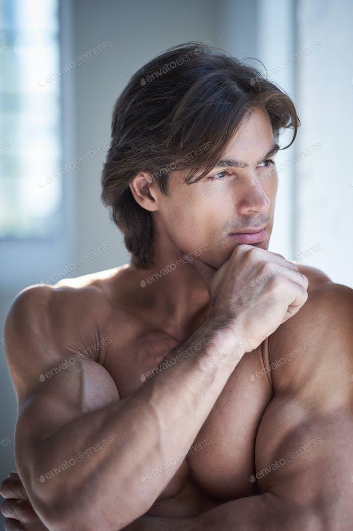 Портрет безрубашечной строганой брюнетки мужчины.