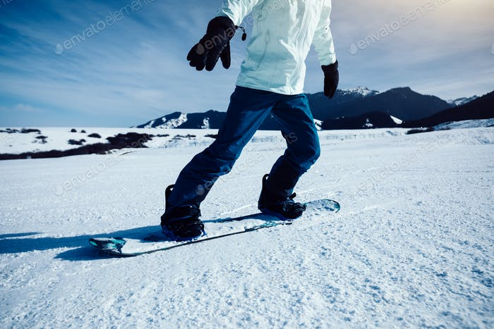 Snowboarder descent on alpine mountain slope
