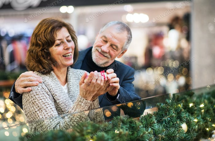 A portrait of senior couple with a present in shopping center at Christmas time.