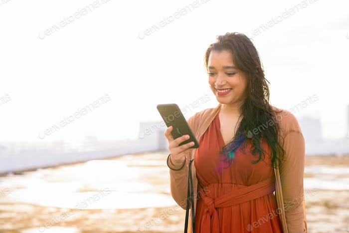 Happy young beautiful Indian woman using phone at rooftop of the building