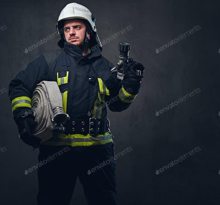 Firefighter in uniform holds fire hose.