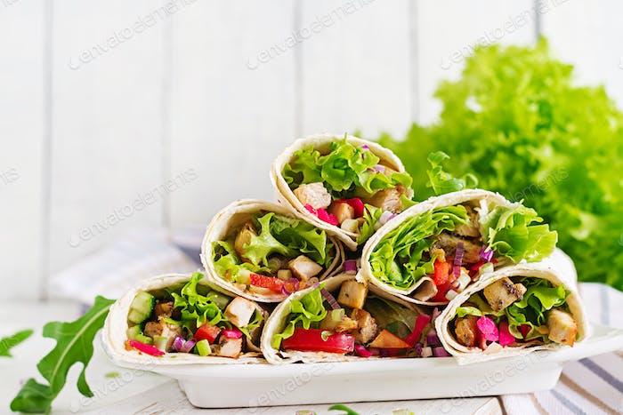 Mexikanische Street Food Fajita Tortilla Wraps mit gegrilltem Hähnchenfilet und frischem Gemüse.