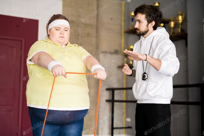 Obese Young Woman Training with Instructor