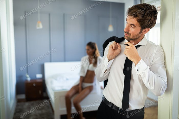 Handsome businessman with young sexy glamorous girl in lingerie