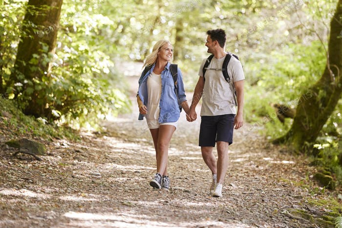 Couple Hiking Along Woodland Path In Lake District UK Together