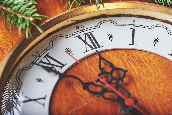 Frohes Neues Jahr um Mitternacht 2018, alte hölzerne Uhr und Tannenzweige