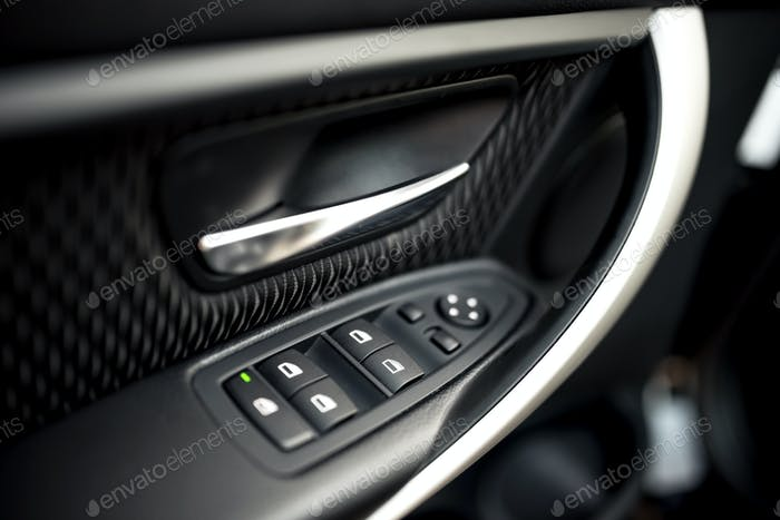 car interior details of door handle with windows controls