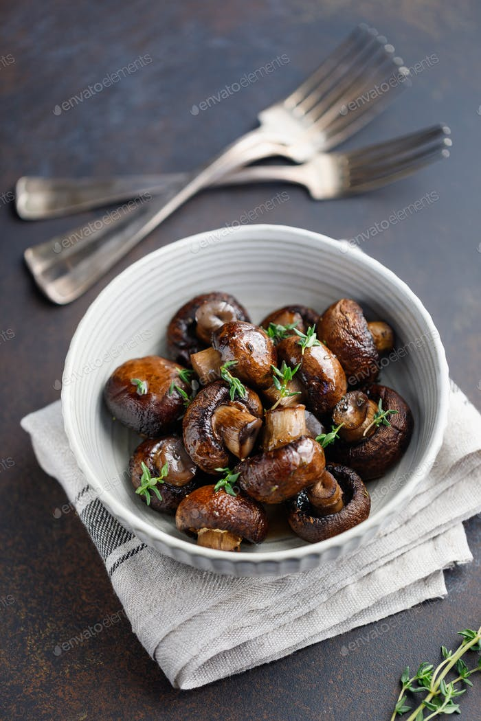 Grilled champignons with thyme in a ceramic bowl. Simple taste recipe.