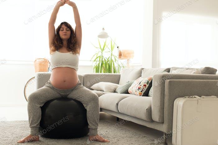 Schwangere Frau tut entspannt Übungen mit einem fitball