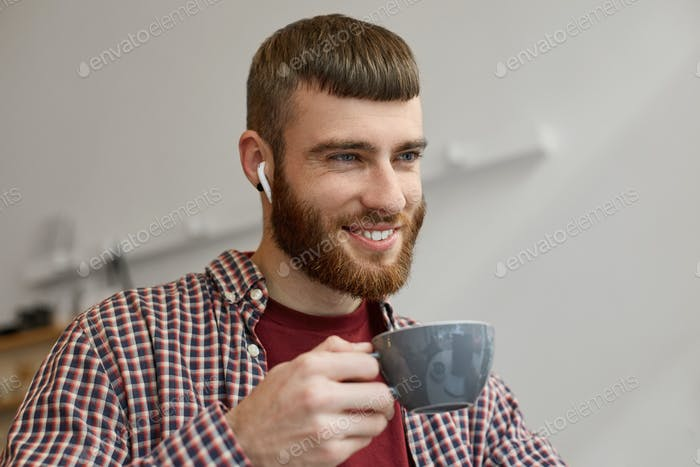 Portrait of a young handsome red-bearded guy broadly smiling and enjoying