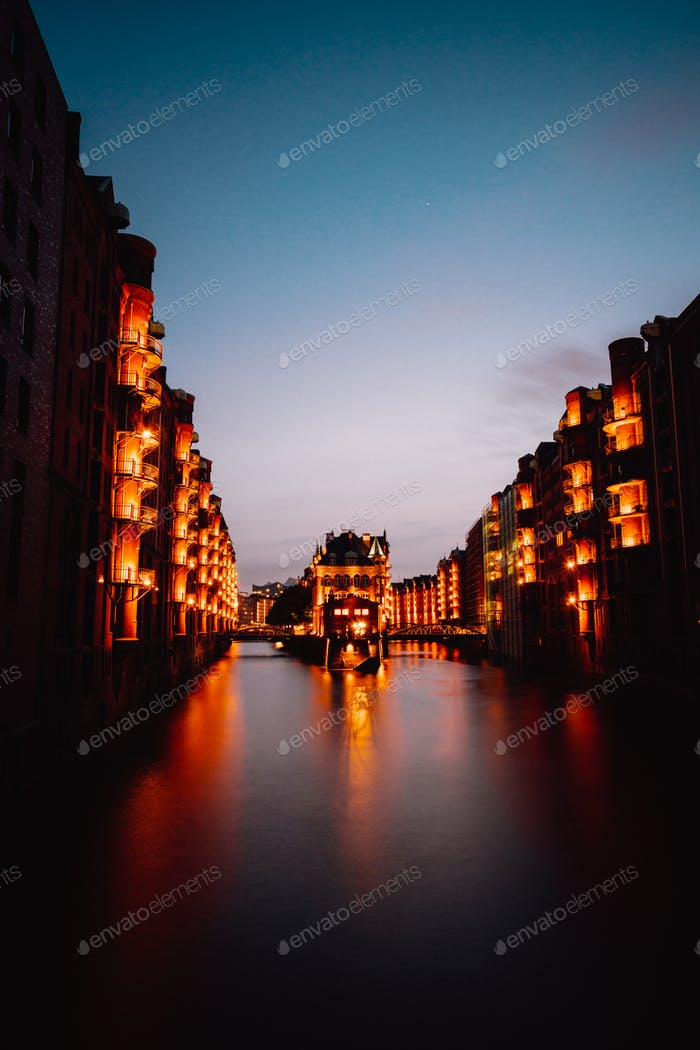 Hamburg, Germany. View of Wandrahmsfleet during sunset with illuminated buildings. Warehouse