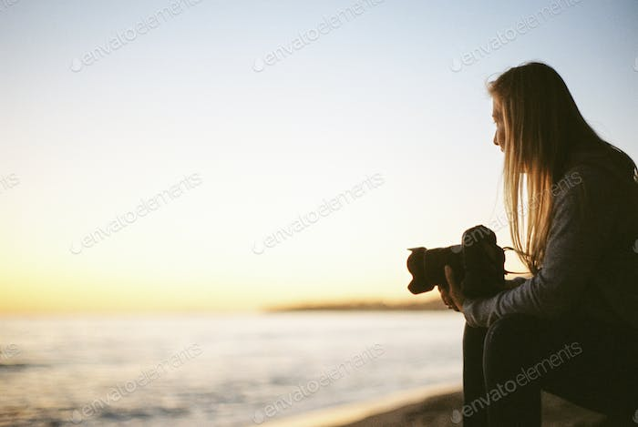 Side view of a woman with long blond hair, sitting on a sandy beach, holding a camera.