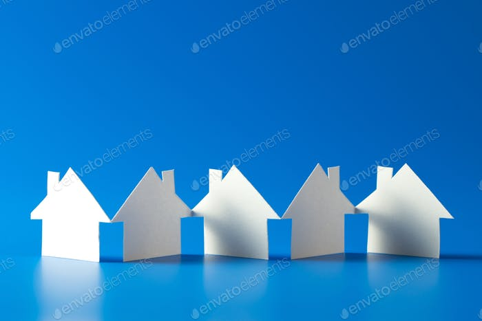 House cut out of paper on blue background