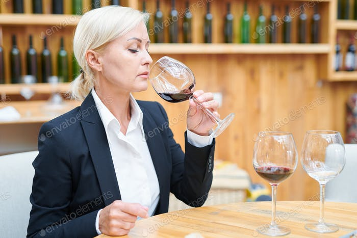 Elegant sommelier sitting by table in cellar and tasting cabernet from wineglass