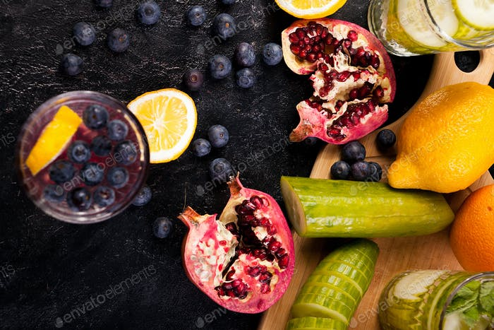 Top view of berries, pomegranate, cucumber and lemons