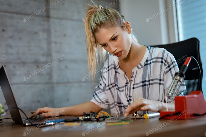 Woman Testing Circuit Board In Her Office