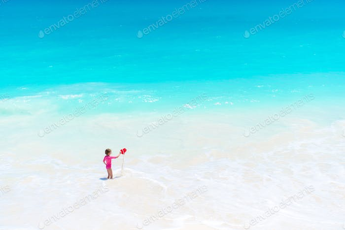 Little girl at tropical white beach having a lot of fun with toys