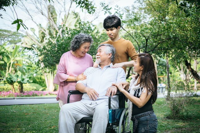 cheerful disabled grandfather in wheelchair welcoming his happy Family