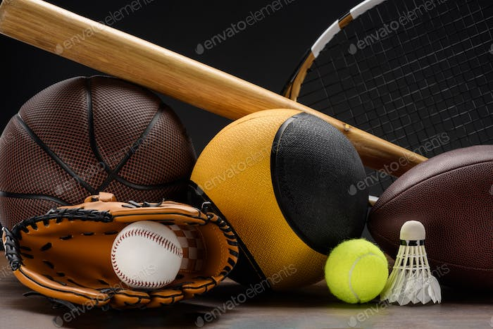Closeup shot of various sports equipment, balls, baseball bat and shuttlecock on wooden surface