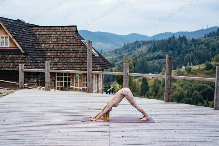 A woman practices yoga at the morning in a terrace on a fresh air