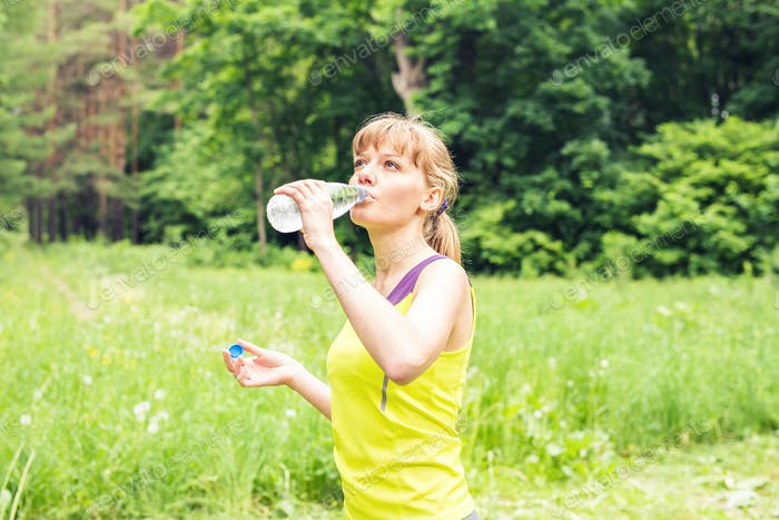 Young beautiful fit woman drink water after her exercise.