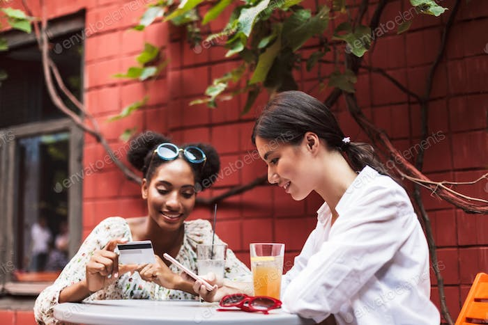 Two pretty smiling girls using cellphone and credit card while h