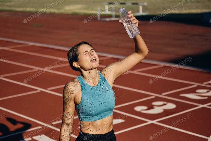 Tired athlete girl in sportswear pouring fresh water on herself after running on city stadium