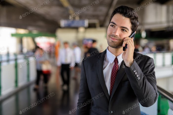 Portrait of businessman in city talking on mobile phone