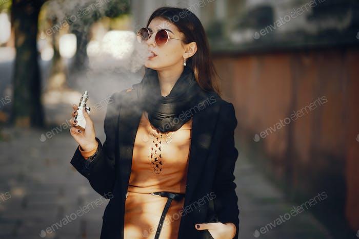 stilvolles Mädchen Rauchen eine E-Zigarette