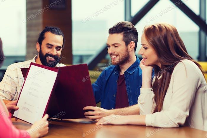 smiling friends discussing menu at restaurant