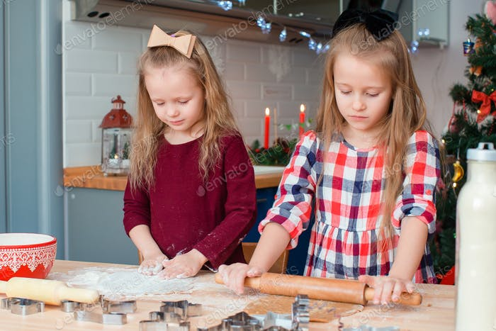 Adorable happy little girls baking Christmas gingerbread cookies in Xmas eve