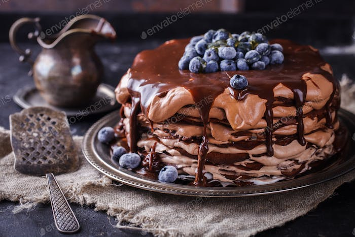 Chocolate cake from chocolate pancakes with icing, with blueberries.