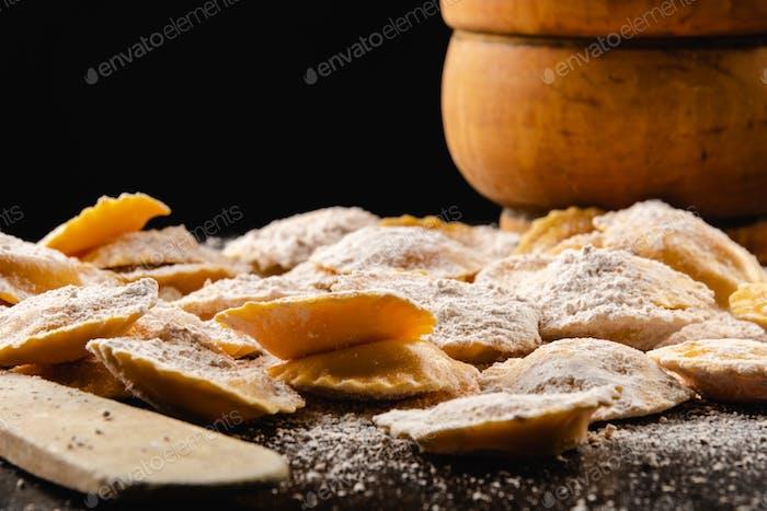 Tasty raw ravioli with flour and basil on wood table