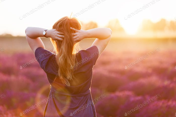 Young woman touching her long sombre hair looking at lavender field at sunset