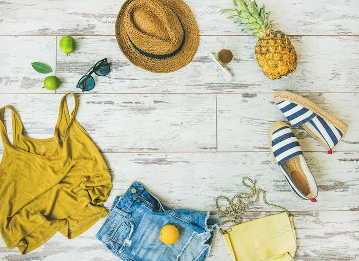 Colorful summer fashion outfit flat-lay over parquet background, copy space