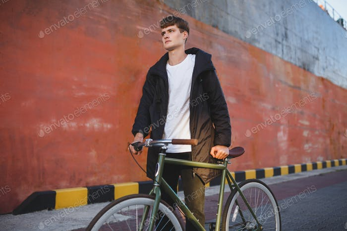 Portrait of young man with brown hair walking with classic bicycle while thoughtfully looking aside