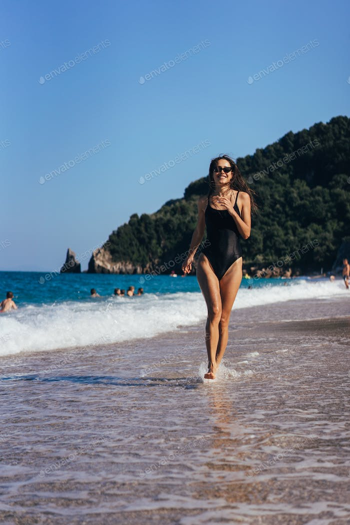 Brunette woman swimsuit and sunglasses runs along seashore