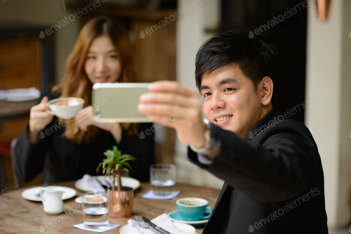 Happy young Asian business couple taking selfie together at the coffee shop