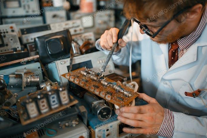 Strange scientist soldering chips, test in lab