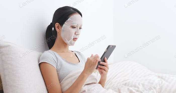 Woman apply facial mask on bed and reading on cellphone