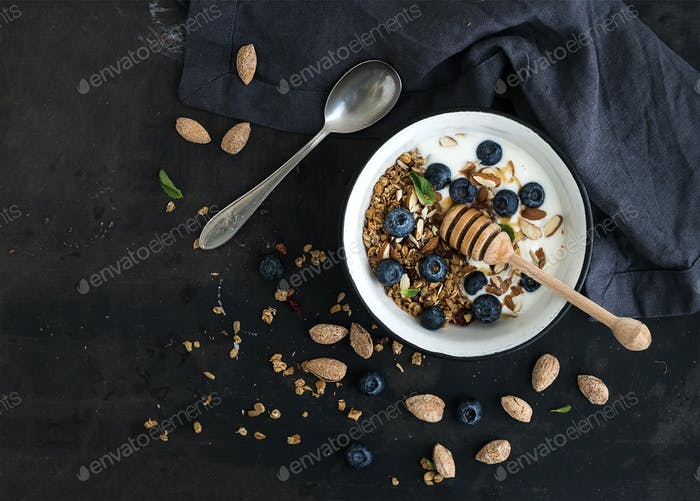 Healthy breakfast. Oat granola with fresh blueberries, almond, yogurt and mint