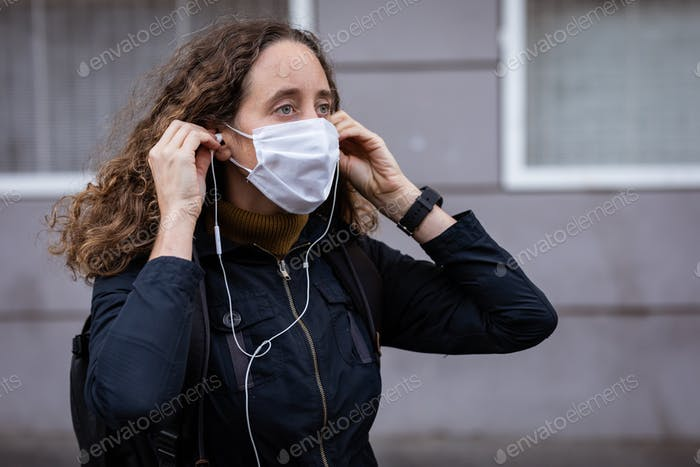 Caucasian woman putting on a protective mask in the streets, wearing earphones