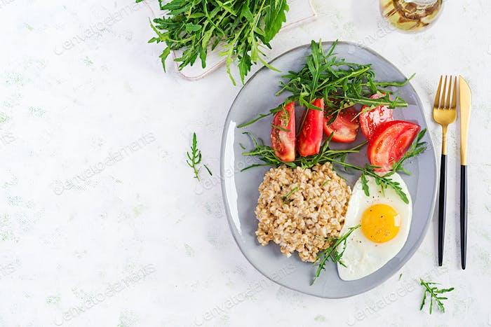 Gachas de avena desayuno con huevo frito, tomates, rúcula
